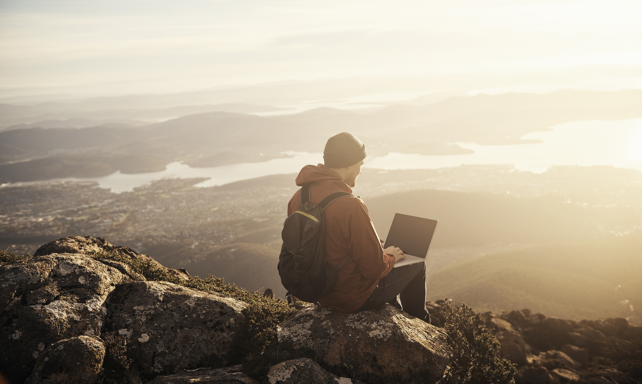 Shot of a person using their laptop on Mount Wellington, with views of Hobart