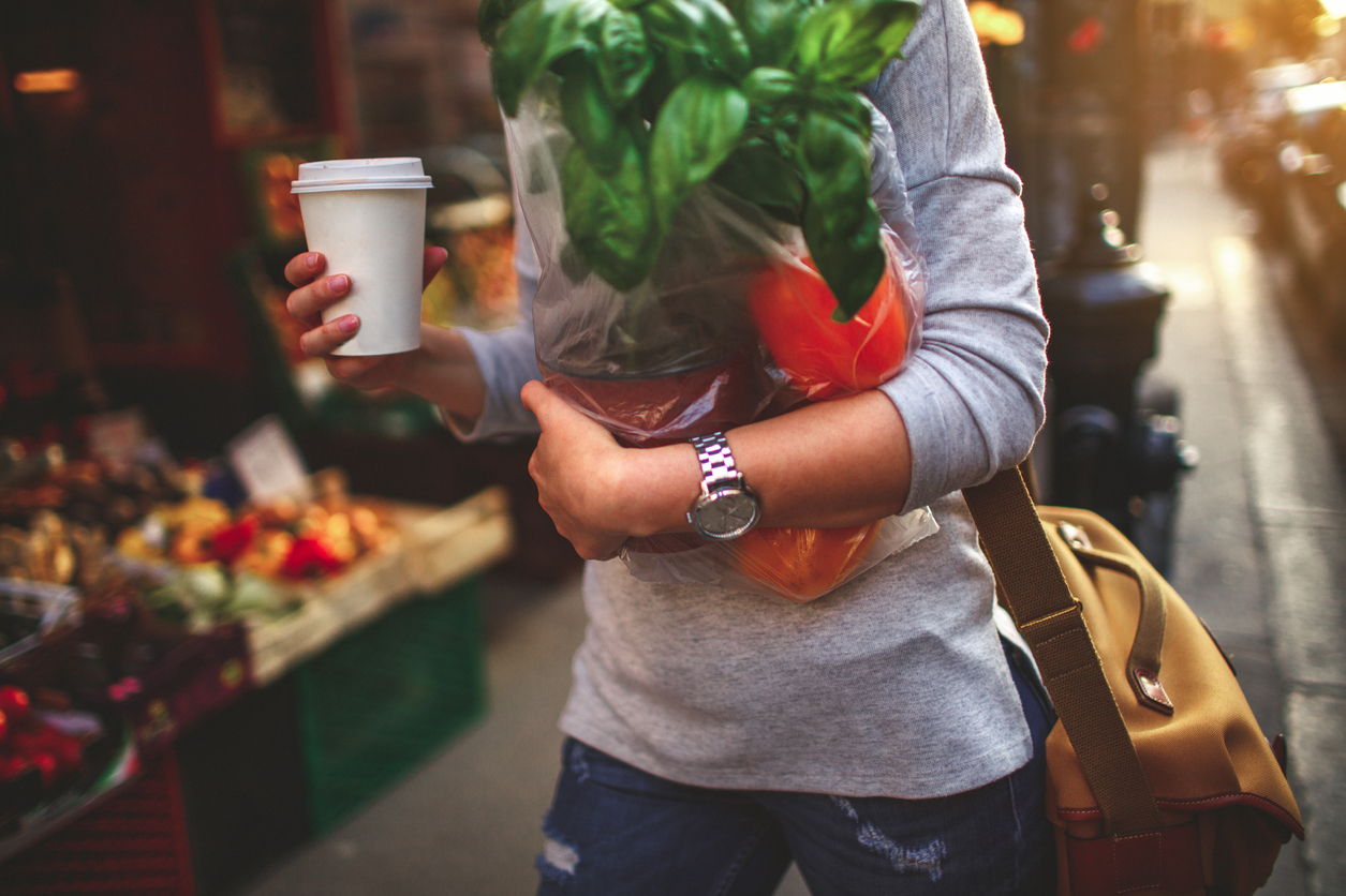 Person carrying a coffee and fresh produce from farmers market